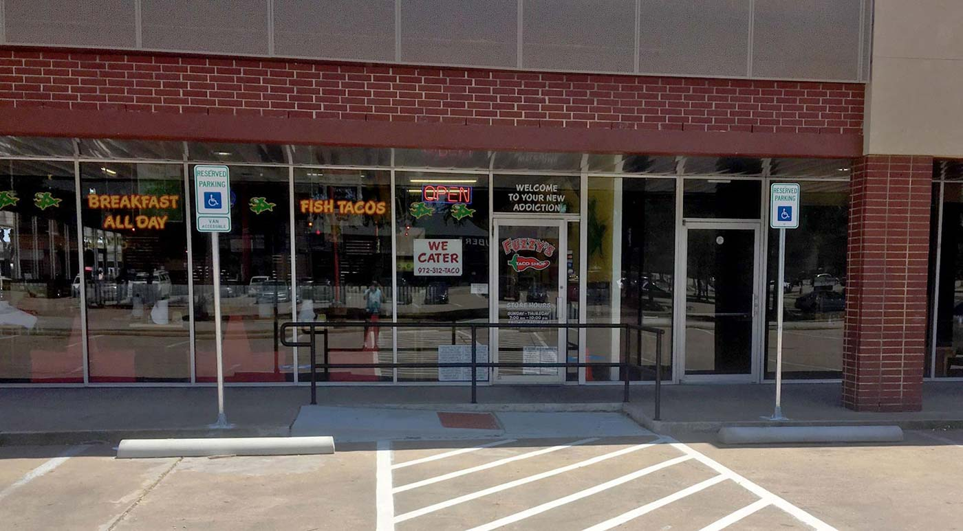Front of store with ADA Signage, wheelchair ramp, handrails, and striping.