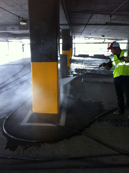 Power washing column with high pressure water in parking garage