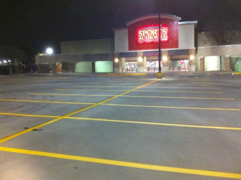 Sports Authority parking lot with yellow parking space striping at night